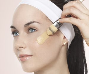 Young lady applying a swatch of foundation